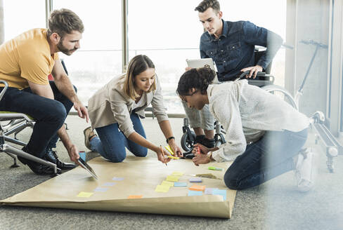 Young business people working together on a project in office - UUF19889