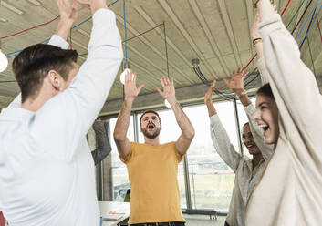 Happy young business people raising their arms in office - UUF19904
