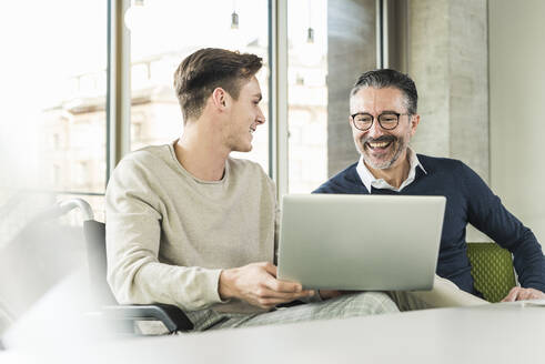 Happy mature businessman and young man in wheelchair using laptop in office - UUF19946