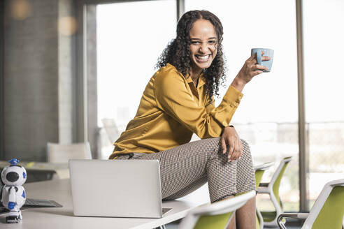 Portrait of happy young businesswoman sitting on desk in office having a coffee break - UUF19961