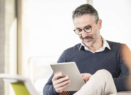 Smiling mature businessman using tablet in office - UUF20003