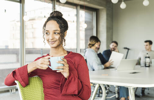 Smiling young businesswoman having a coffee break during a meeting in office - UUF20021