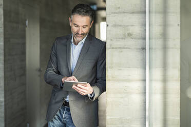 Mature businessman leaning against a wall in office using tablet - UUF20042