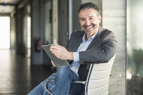 Portrait of a happy mature businessman with tablet sitting on chair in office - UUF20045