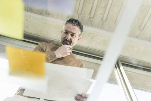 Mature businessman working on adhesive notes on glass table in office - UUF20051