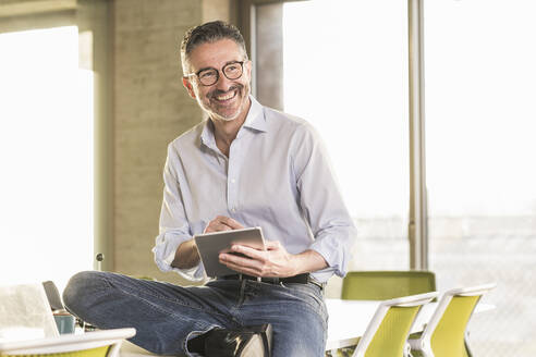 Happy mature businessman with tablet in office - UUF20060