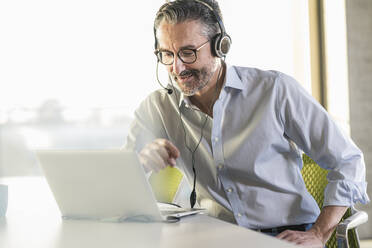 Mature businessman wearing headphones using laptop at desk in office - UUF20066