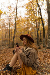Fashionable redheaded young woman sitting in autumnal forest looking at cell phone - AFVF04885