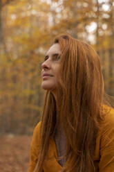 Portrait of redheaded young woman in autumnal forest - AFVF04894