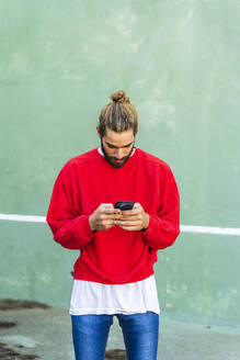 Bearded young man with dyed hair wearing red sweatshirt  in front of green wall using cell phone - AFVF04921