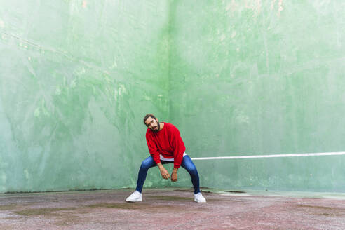 Portrait of bearded young man wearing red sweatshirt standing in front of green wall - AFVF04924