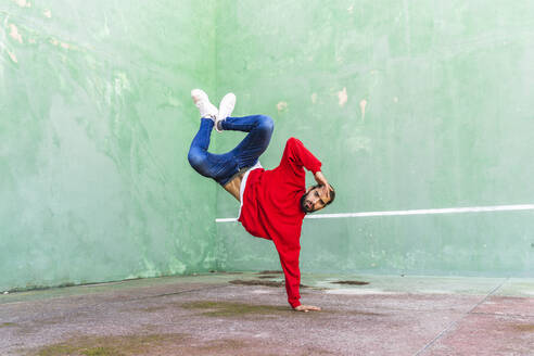 Portrait of bearded young man wearing red sweatshirt doung handstand on one hand - AFVF04927