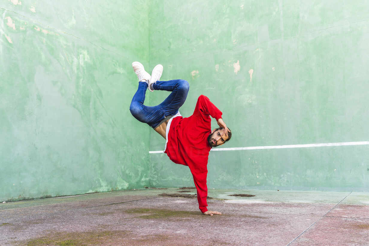 Portrait of bearded young man wearing red sweatshirt doung handstand on one hand - AFVF04927 - VITTA GALLERY/Westend61