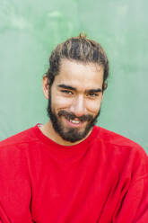 Portrait of bearded young man with dyed hair wearing red sweatshirt - AFVF04930
