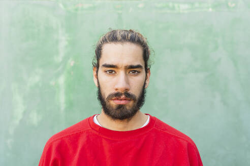 Portrait of bearded young man wearing red sweatshirt in front of green wall - AFVF04933