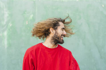 Bearded young man with tossing his hair in front of green wall - AFVF04936