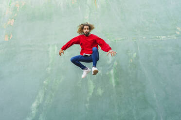 Portrait of young man wearing red sweatshirt jumping in the air in front of green wall - AFVF04939