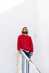 Portrait of bearded young man wearing red sweatshirt standing on stairs looking at distance - AFVF04945