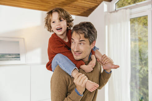 Father carrying daughter on shoulders at home - MFF04982