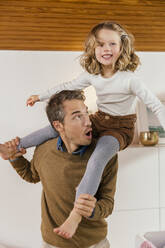 Happy father carrying daughter on shoulders at home - MFF04985