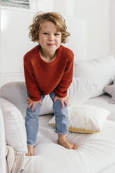 Portrait of smiling girl standing on couch at home - MFF04997