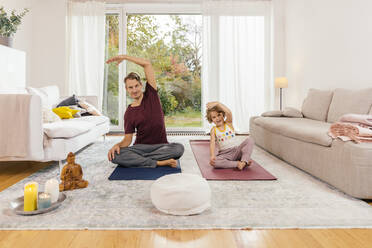 Father and daughter doing yoga together at home - MFF05012