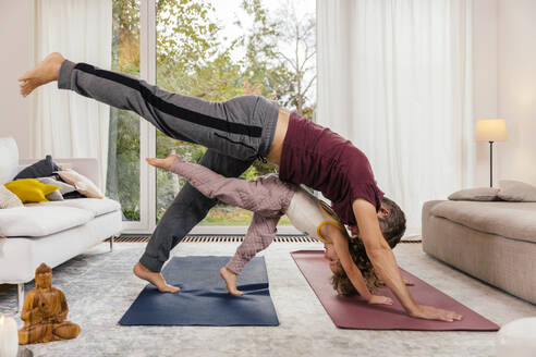 Father and daughter doing yoga together at home - MFF05015
