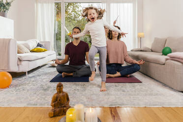 Exuberant girl with parents meditating at home - MFF05021