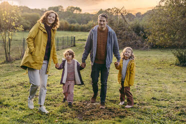 Portrait of happy family with two daughters walking on a meadow in autumn - MFF05024