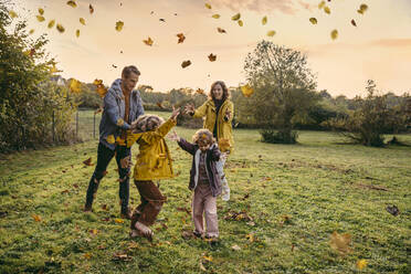 Happy family playing with autumn leaves on a meadow - MFF05030