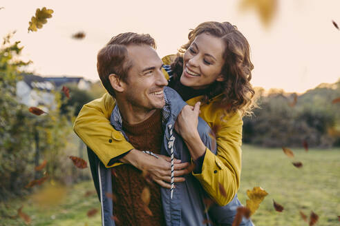 Man giving woman a piggyback ride outdoors in autumn - MFF05036