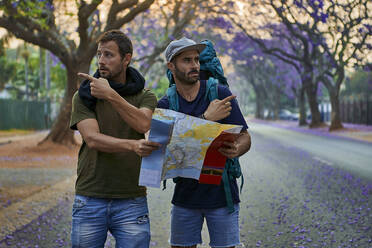 Backpackers with map on a street, Pretoria, South Africa - VEGF01263