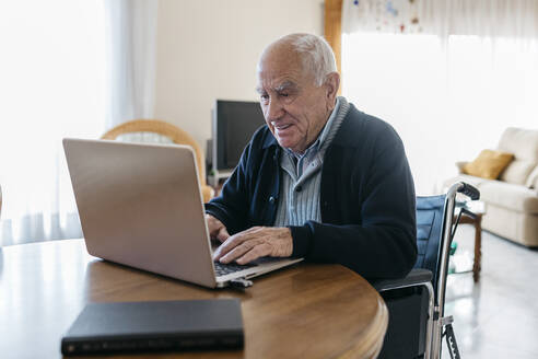 Portrait of content senior man in wheelchair using laptop at home - JRFF03935