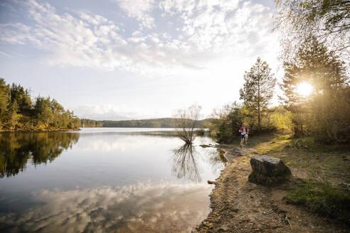 Man running at the lake at sunset, Forstsee, Carinthia, Austria - DAWF01085