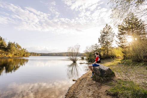 Sportive man sitting on a rock at the lakeside at sunset, Forstsee, Carinthia, Austria - DAWF01088