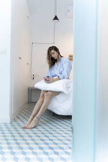 Young woman sitting on bed and using smartphone in the morning - ERRF02529