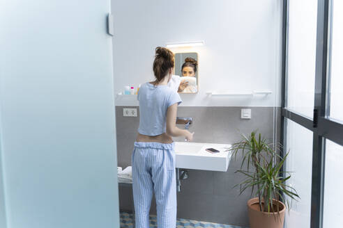 Rear view of young woman brushing teeth in bath room - ERRF02553