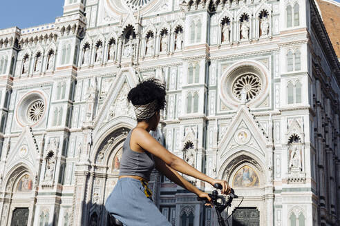 Young woman riding bicycle in front of cathedral, Florence, Italy - SODF00490