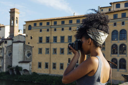 Young woman taking photo with camera, Florence, Italy - SODF00493