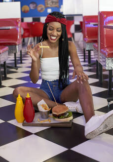 Young woman with braided hairstyle sitting on the floor with her hamburger plate and eating a chip - VEGF01275