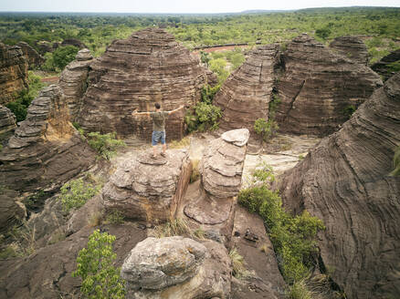 Burkina Faso, Man with arms outstretched on top of rock at Domes of Fabedougou - VEGF01281