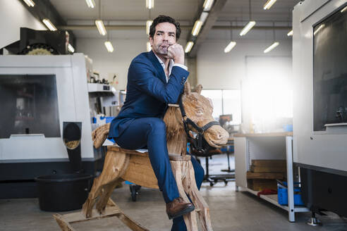 Pensive businessman on wooden rocking horse in a factory - DIGF09047
