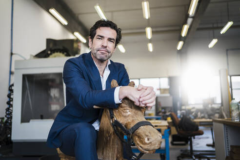 Portrait of a businessman on wooden rocking horse in a factory - DIGF09050