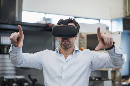 Businessman using VR glasses in a factory - DIGF09062