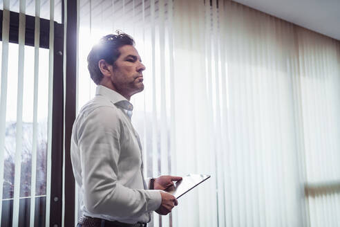 Businessman holding tablet at the window in office - DIGF09125