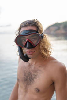 Young man with snorkel on beach - AFVF04978