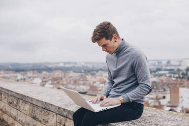 Blond young man sitting on a wall and typing on his laptop in Lleida - ACPF00652