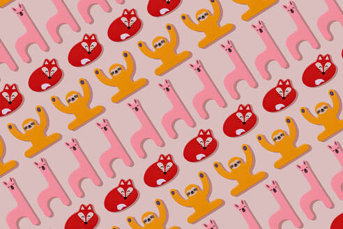 Llama, fox and sloth, wooden toys in a row on pastel pink background - GEMF03402