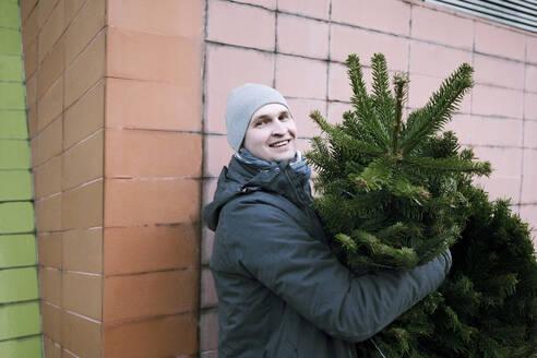 Smiling man with fir tree - EYAF00792