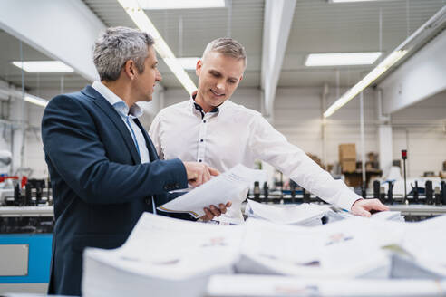 Two businessmen discussing paper in a factory - DIGF09132